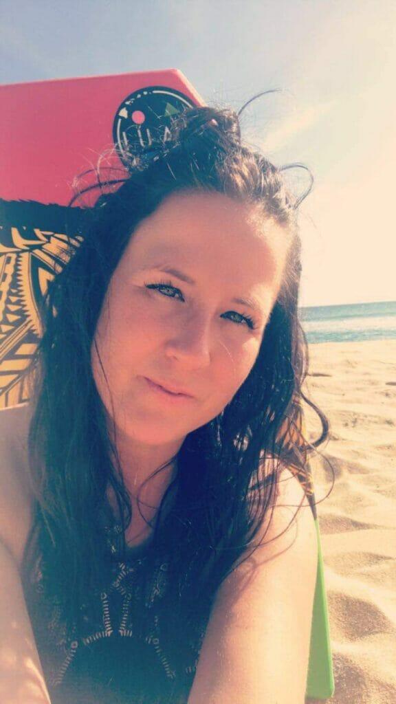 Annne St-Amand - À la plage en avant d'une planche de surf